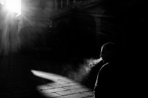 picture of man in shadows in a street, smoking