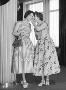picture of two women in party dresses from 1956, one whispering in the ear of the other