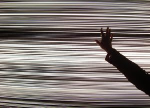 Screen with horizontal lines on it, lots of bands of light and dark, and a hand and arm in front of it, silouetted against it