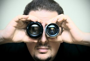 man holding camera lenses in front of each of his eyes so they look like his eyes